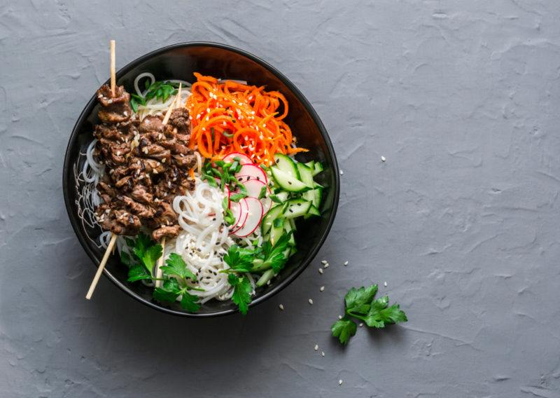 A black bowl that contains various asian ingredients, including beef