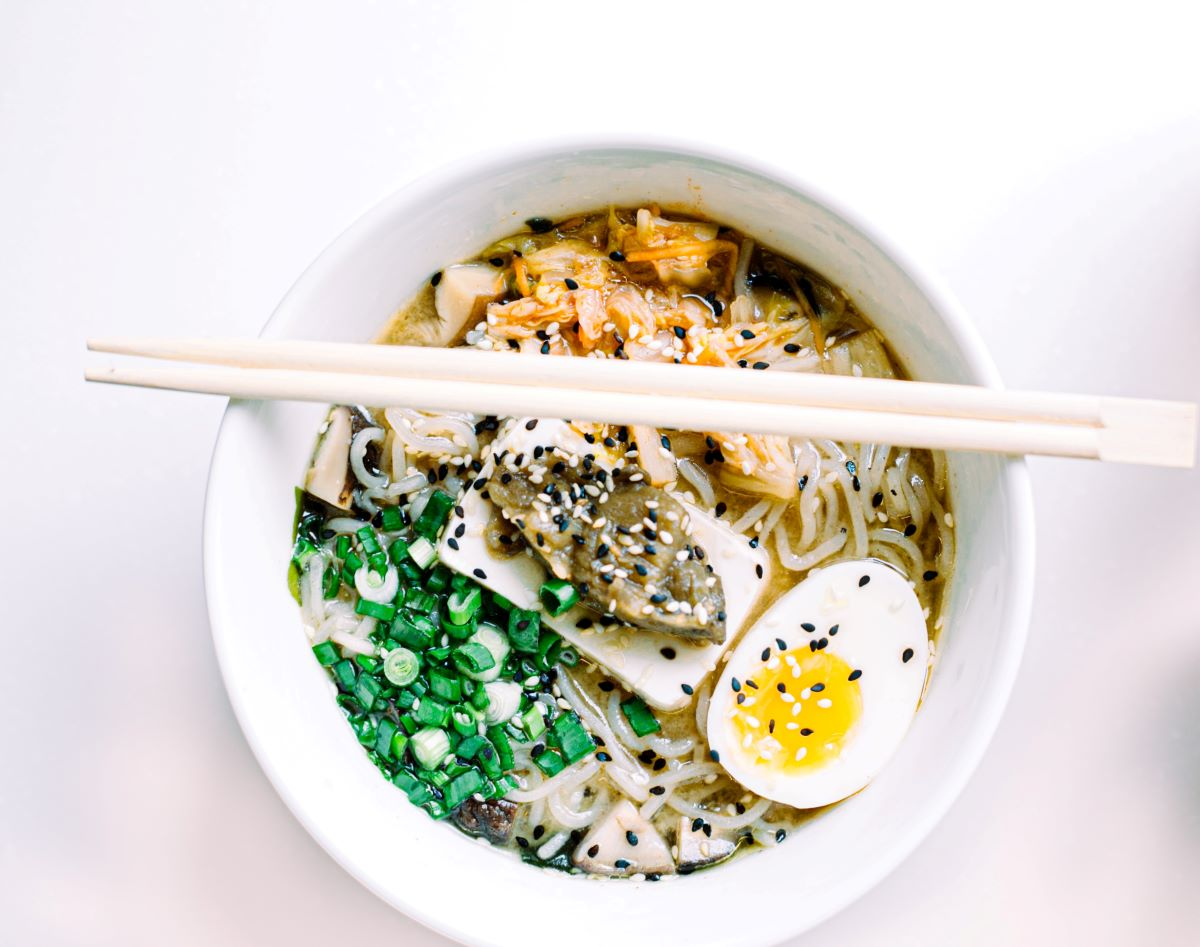 Ramen of the Month Clubs - white background, white bowl with ramen garnished with sesame seeds, hard boiled egg, and green onions, with chopsticks laying across the top
