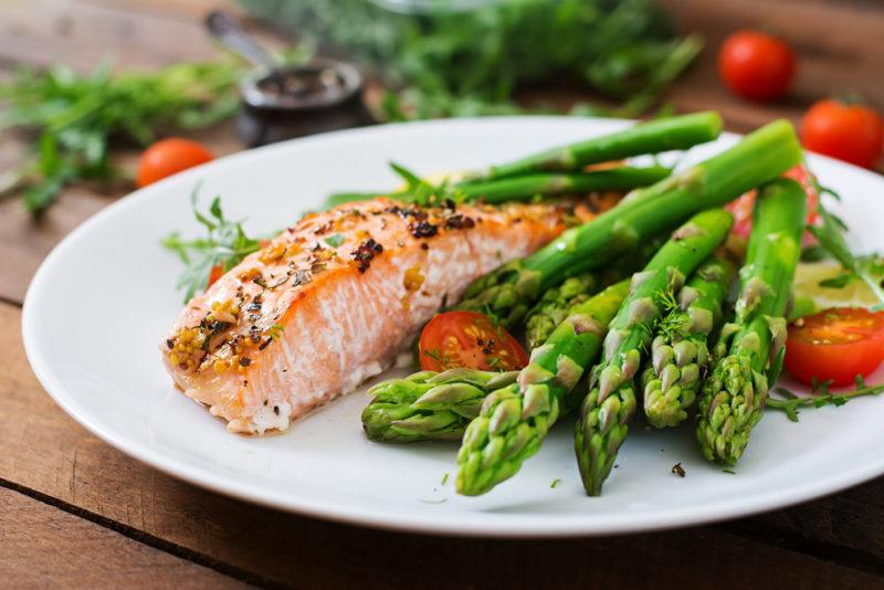 A white plate with a dinner of cooked salmon and asparagus