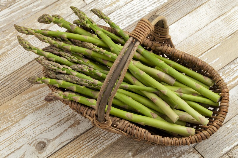 Several spears of asparagus like in a brown wicker basket on a wooden background.