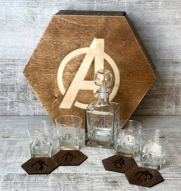 Four whiskey glasses, four coasters and a decanter, all themed around the Avengers
