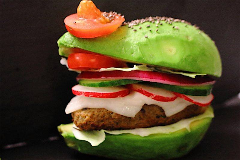 A burger using avocados as buns and containing plenty of veggies