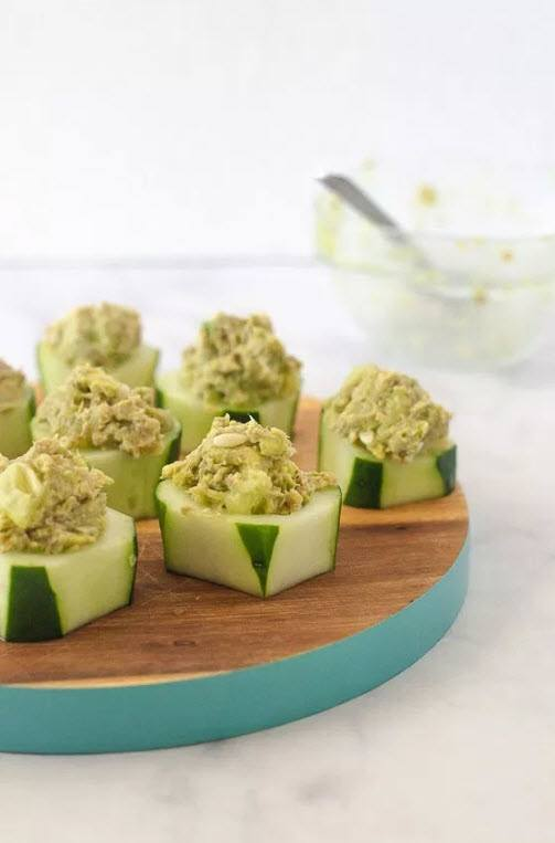 Cut pieces of cucumber with avocado salmon mix