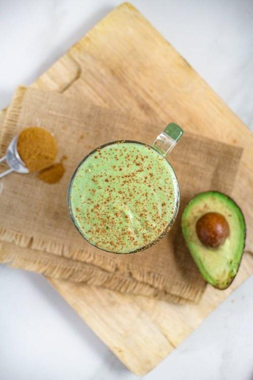 A green smoothie with cinnamon and avocado on a cutting board.