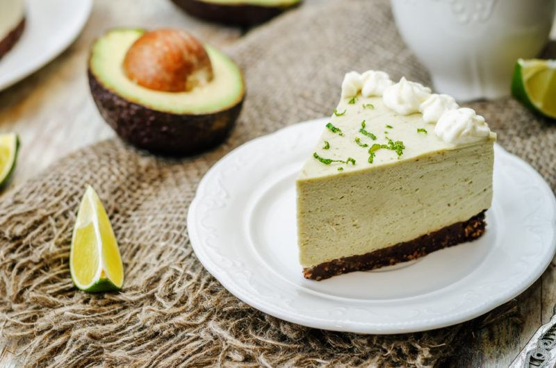 An avocado cheesecake on a white plate with avocado next to it