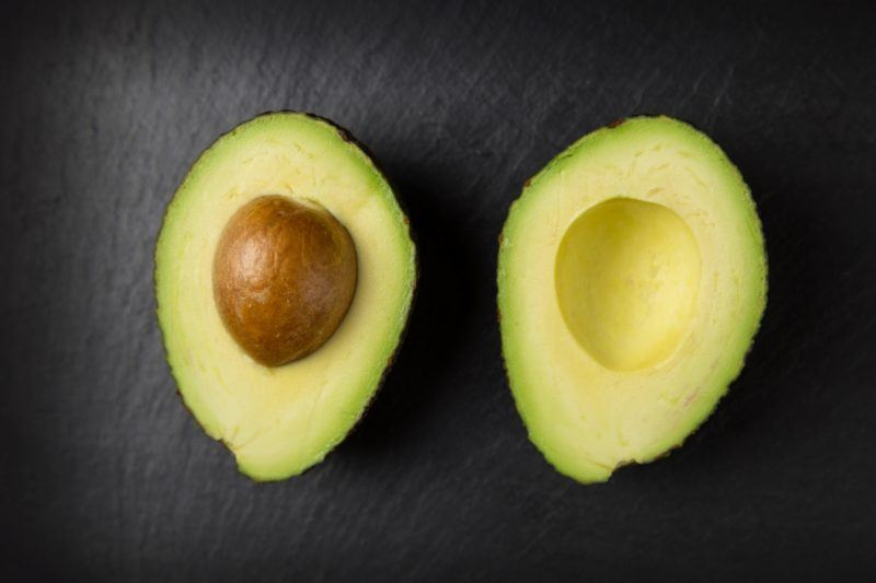 An avocado cut in half on a black background