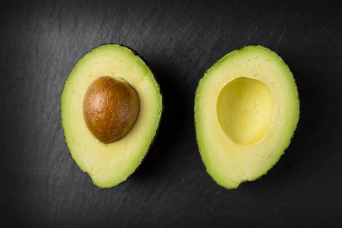 Photo of an Avocado cut in half length-wise on a black background, representing the Avocado of the month club