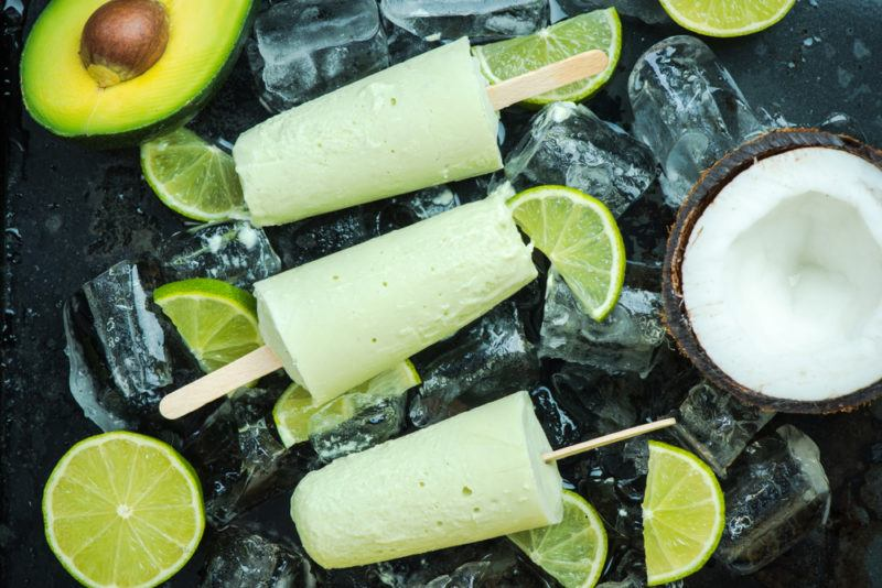 Three avocado popsicles against a black background with ice and lime