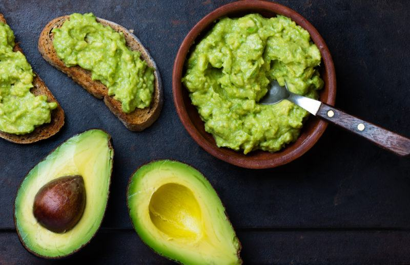 A bowl of mashed avocado, an avocado that has been cut open and avocado on toast