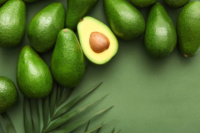 Various whole avocados on a green background with a branch from a tree and one avocado that has been cut in half