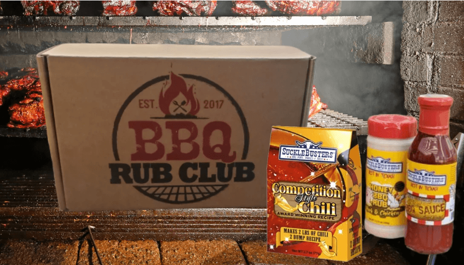 In the background a smoker with shelves of meat.  In front a cardboard box that says est 2017 BBQ Rub Club and on the right lower corner a competition style chili kit, honey bbq rub. and bbq sauce