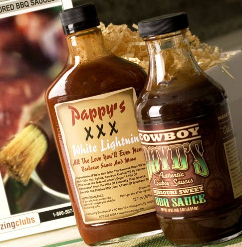 2 bottles of BBQ sauce in front of a computer monitor