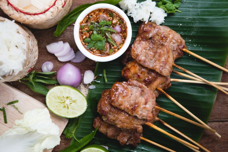 Thai BBQ meat on a stick next to seasonings