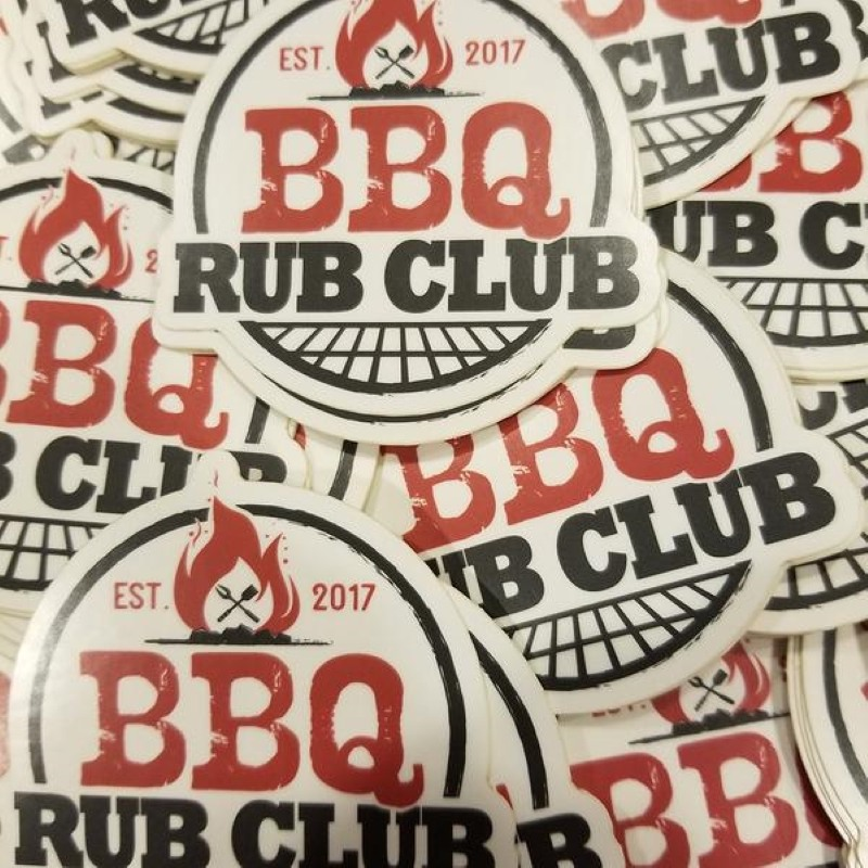 A pile of stickers - The stickers are mostly round, with a white background, at the top in red it says est. 2017 with a bonfire in between the year and est.  Then in large Red Font it says BBQ, below that in Black font Rub Club and at the bottom a grill grate.