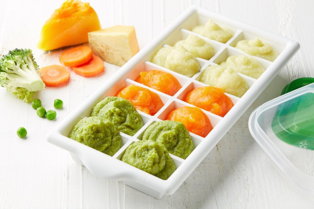 A white ice cube tray with three types of baby food