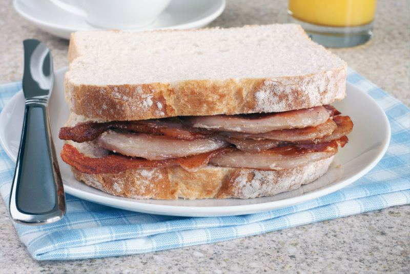 A bacon sandwich with white bread on a white plate