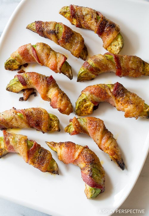 A white plate with avocado pieces that are wrapped in bacon.