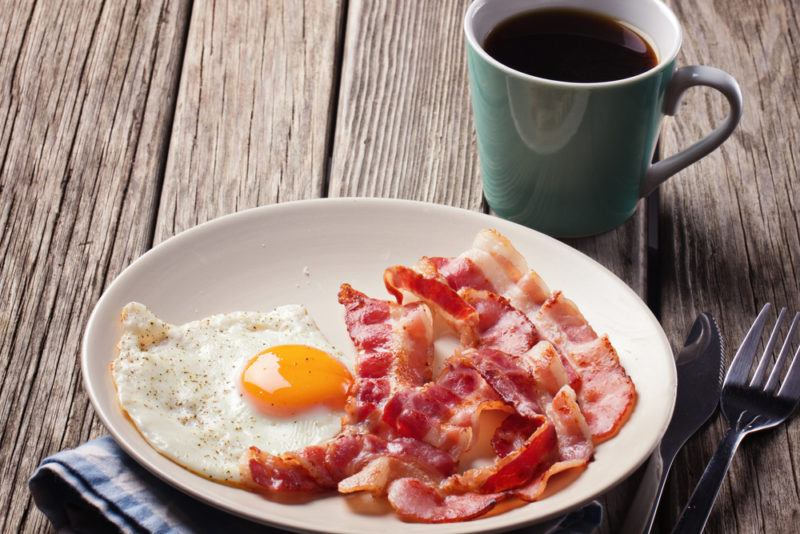 A fried egg and bacon on a plate with a mug of coffee in the background