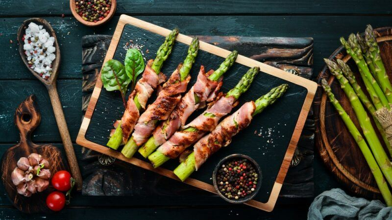 A slate and wood tray with five pieces of bacon wrapped asparagus