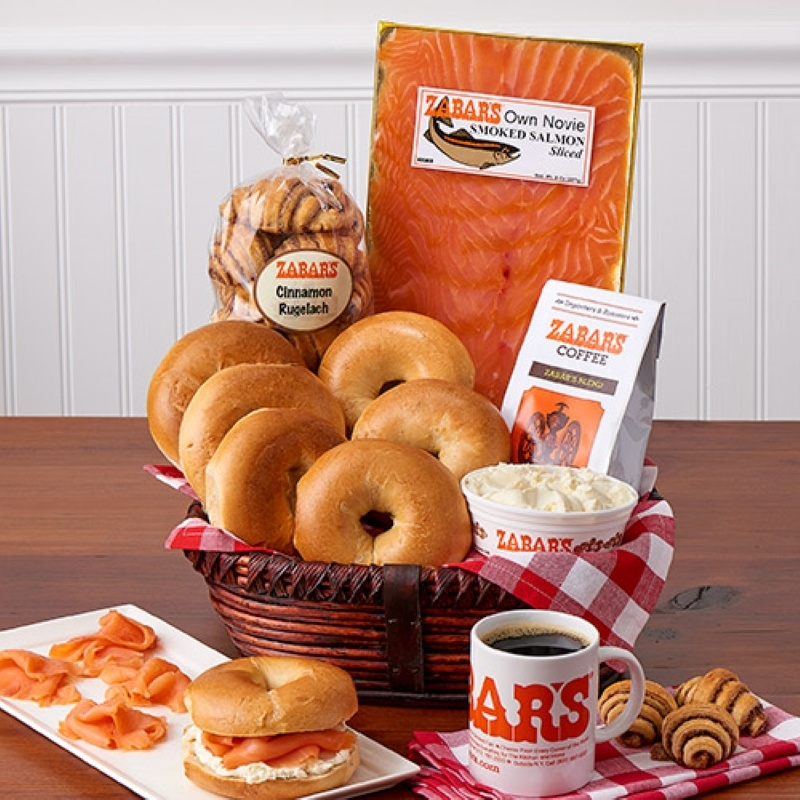 Zabar's Gift basket lined with a red and white napkin containing a bag of rugelach, package of lox, 6 bagels, a bag of coffee, an open container of plain cream cheese sitting in front of the basket is a white plate with a bagel with cream cheese and lox, plus 4 pieces of lox and a full coffee cup and three rugelach on a red and white napkin