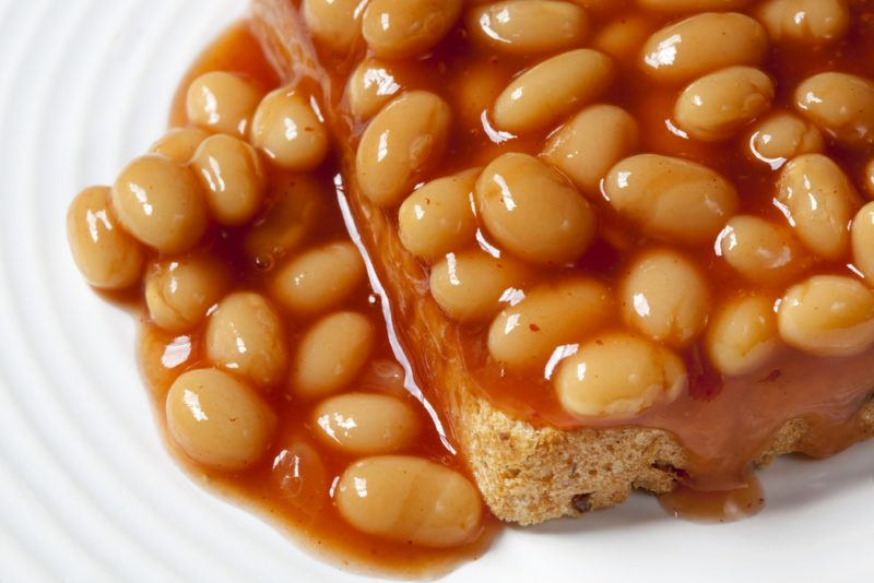 A white plate with baked beans on toast