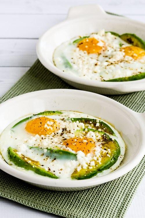 Two white bowls with avocado, eggs and feta