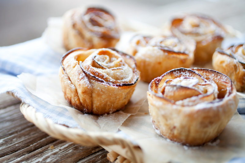 Six baked apple roses on a wooden table