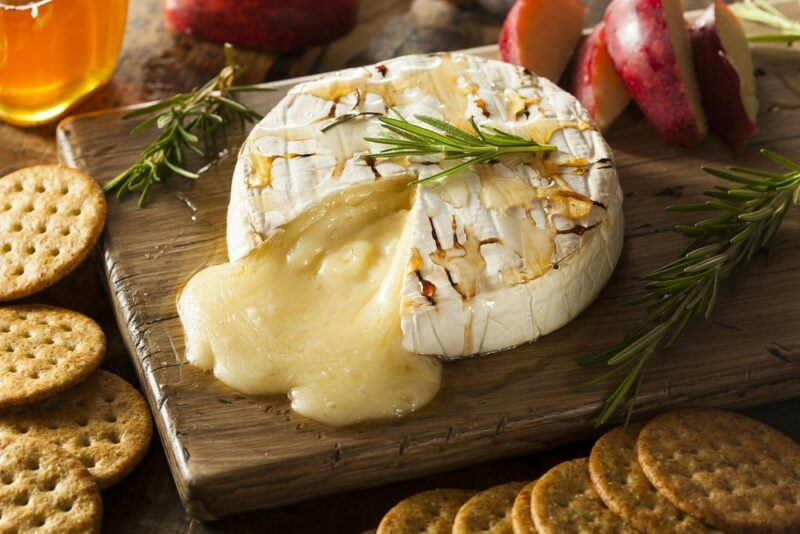 A wooden board with a wheel of baked brie that is melting