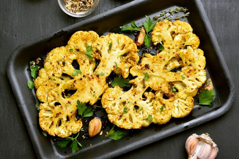A black baking tray with cauliflower that has been sliced in half, seasoned, and baked