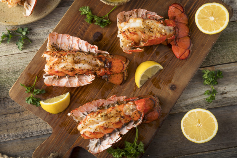 Three baked and seasoned lobster tails on a wooden board with herbs and lemon wedges