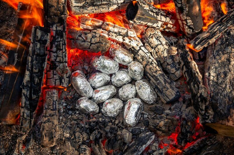 A selection of baked potatoes in tin foil that are cooking in the embers of a fire