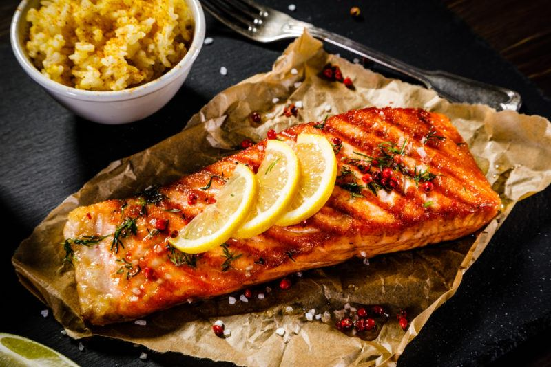 Baked salmon with lemon on baking paper with a small bowl of rice