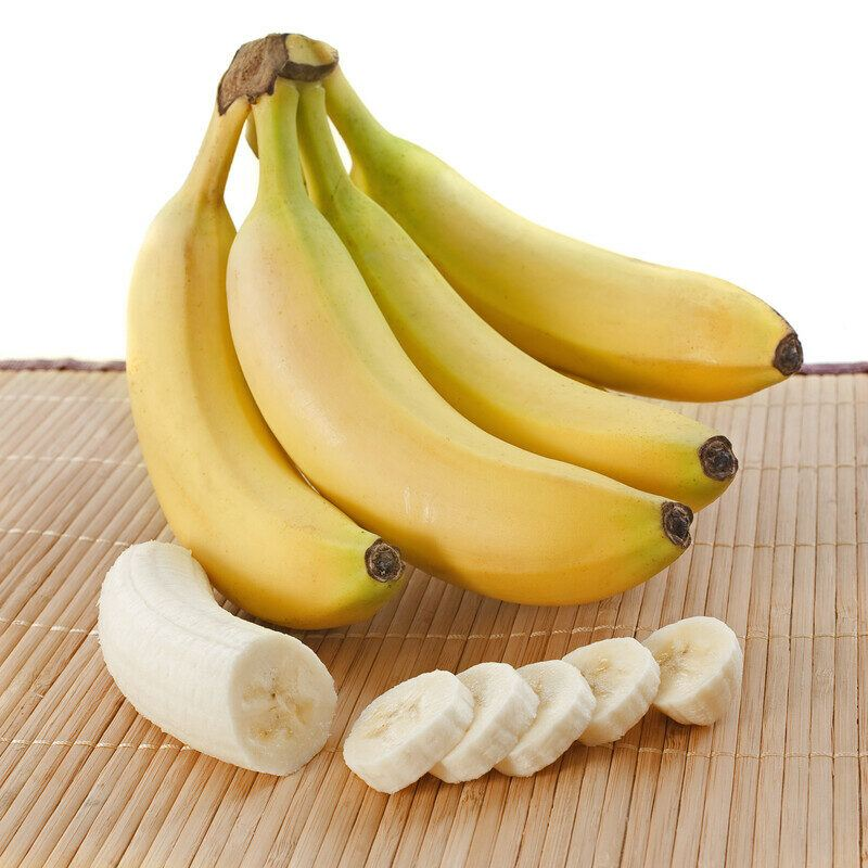 This photo shows a bunch of bananas and a sliced banana on a bamboo mat against a white background.