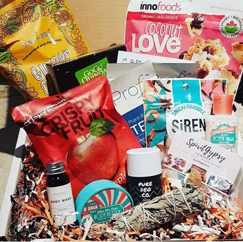 A collection of snacks and body products in a box