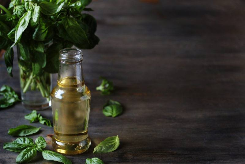 A bottle of simple syrup infused with basil, with basil leaves in the background