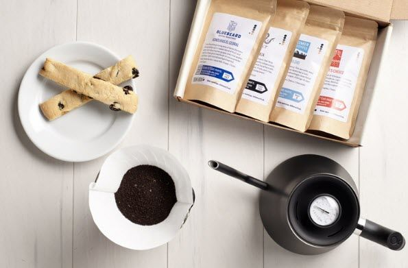 Selection of 4 coffees in a box with various other items.