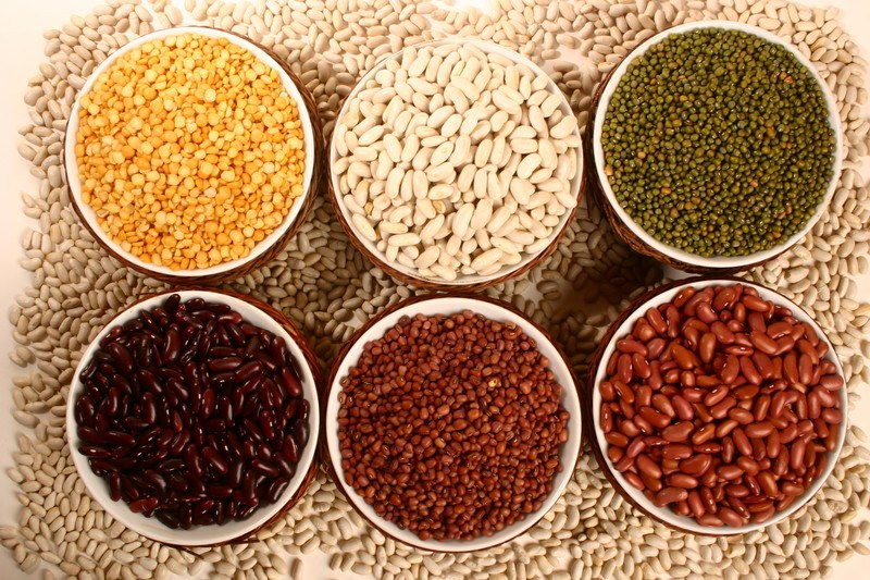 Six bowls containing a variety of legumes in yellow, white, green, brown, and red colors are surrounded by loose white beans.