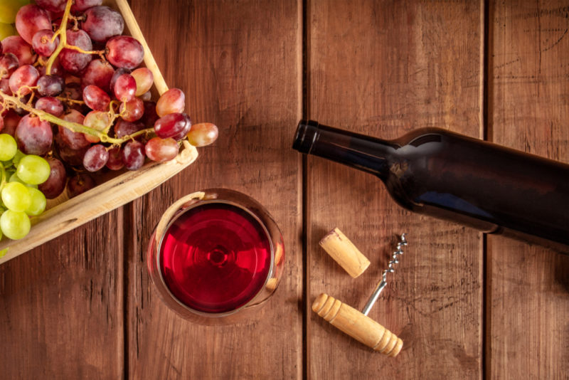 A wooden table with a bottle of Beaujolais wine, a glass of the wine, a cork, corkscrew, and a box of grapes