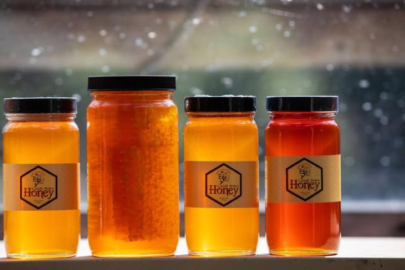 4 jars of honey in a window sill - the second jar is larger with a honey and honeycomb inside.  The other three jars have the Bee Country label