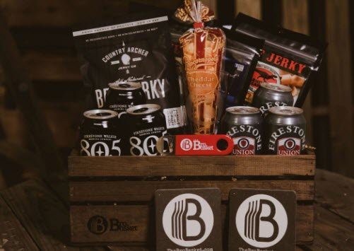 A dark wooden crate containing 6 cans of beer, popcorn and plenty of jerky. There are two coasters resting on the front of it and a bottle opener on top.