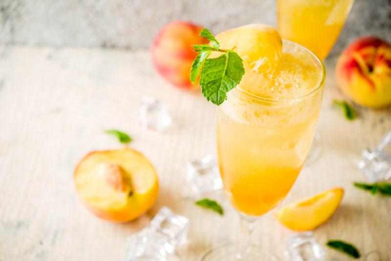 A peach bellini with ice and peaches on a table