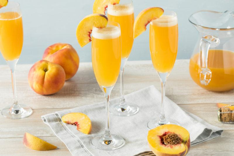 Various glasses of Bellini and peaches on the table