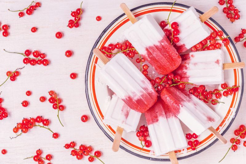 A plate of berry and yogurt popsicles with berries scattered around a white table