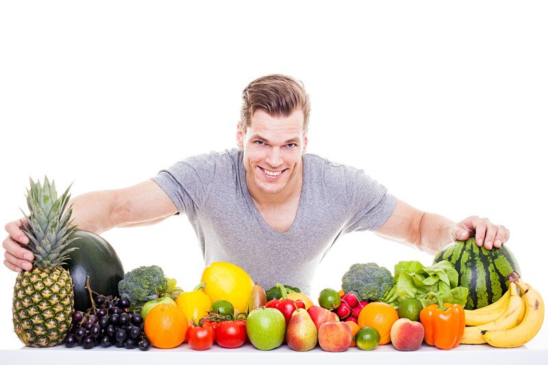 This photo shows a smiling young man in a gray shirt behind a row of several fruits and vegetables, representing the best foods for men's health.