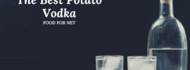 A bottle of potato vodka next to two glasses against a black background