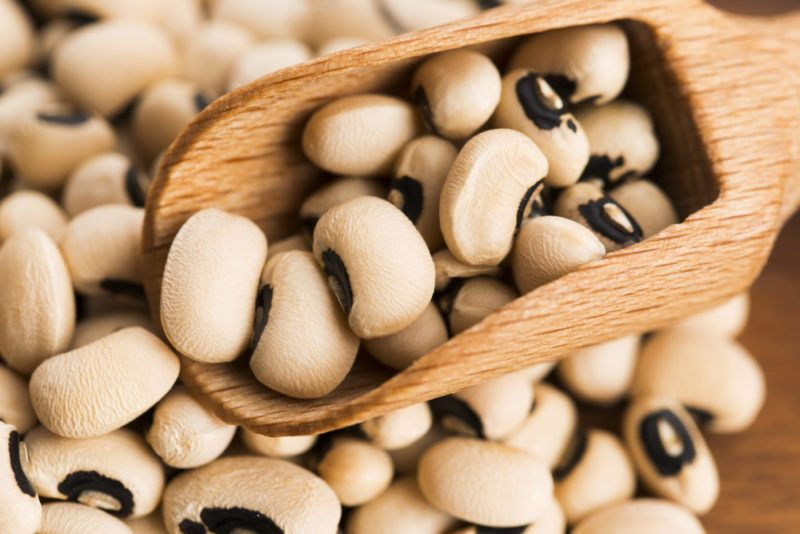 A pile of black eyed peas and a wooden scoop