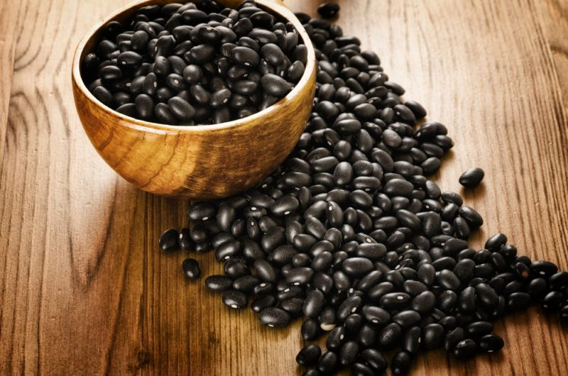 Black turtle beans on a table and in a wooden bowl
