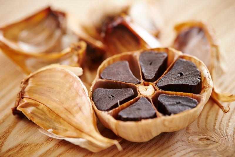 A cut open bulb of black garlic on a table