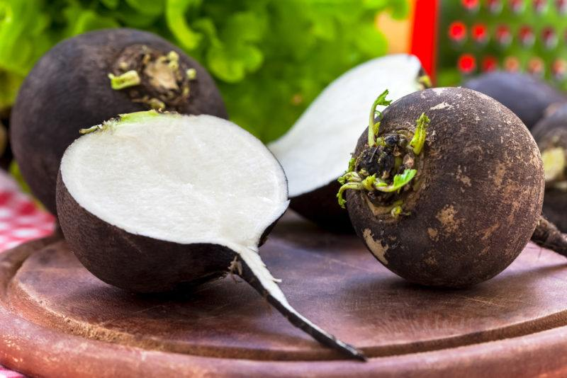 Black radishes, where one of them has been cut open, exposing a white interior