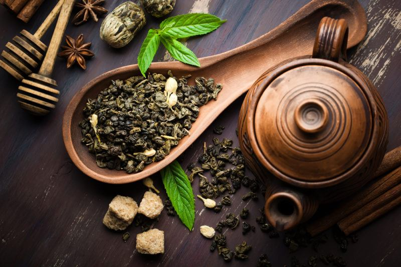 A wooden spoon with black tea leaves, on a table that also has fresh tea leaves, sugar, and a pot of some kind